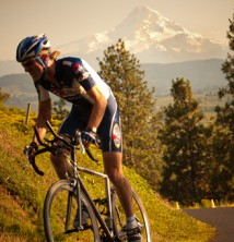 Mountain biker on country road with Mt. Hood in background