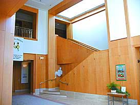 The lobby of the archives building has light colored wood walls, a staircase up to 2nd floor. In the corner a sculpture of woman