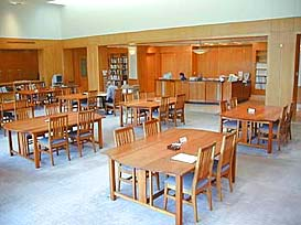 Several wooden tables and chairs fill the reference room.