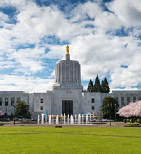 Oregon State Archvies image of capitol building with blue sky, clouds and trees in blossom.