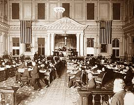 Photo of the Senate Chamber in 1895 in Salem Oregon. There are dozens of men at desks in a large, high ceiling room.