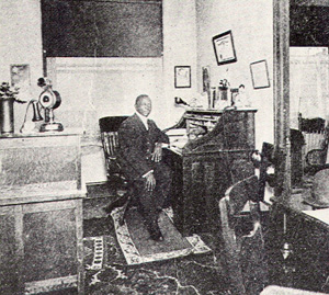 Photo of a black man sitting at a desk in a journalist office.
