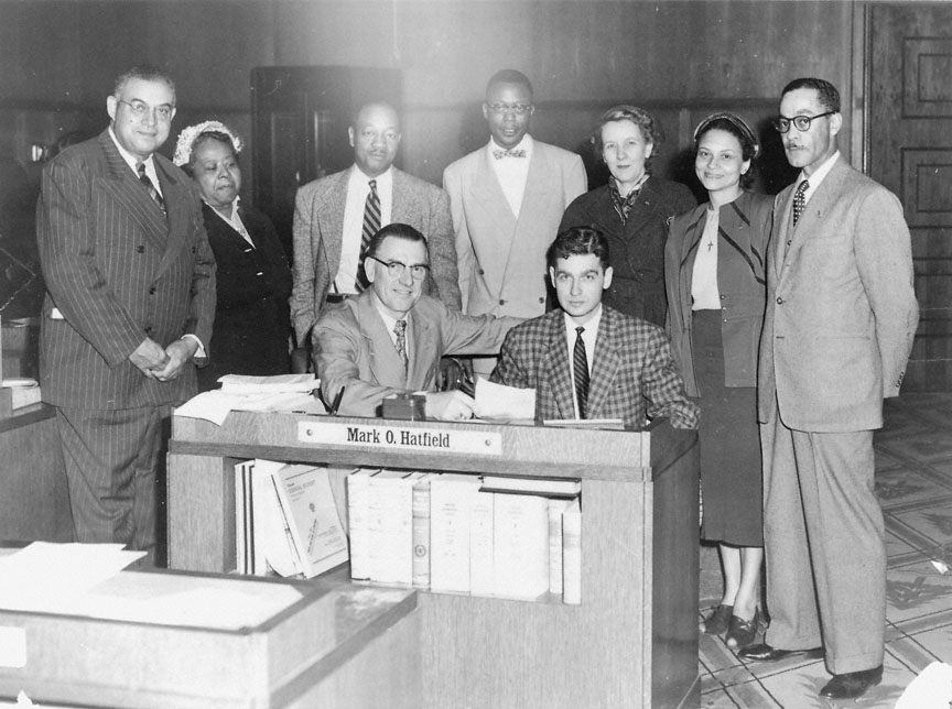 Photo of 2 Mark Hatfield sitting at a desk with another white man. Behind them stand 3 black men and 3 women.