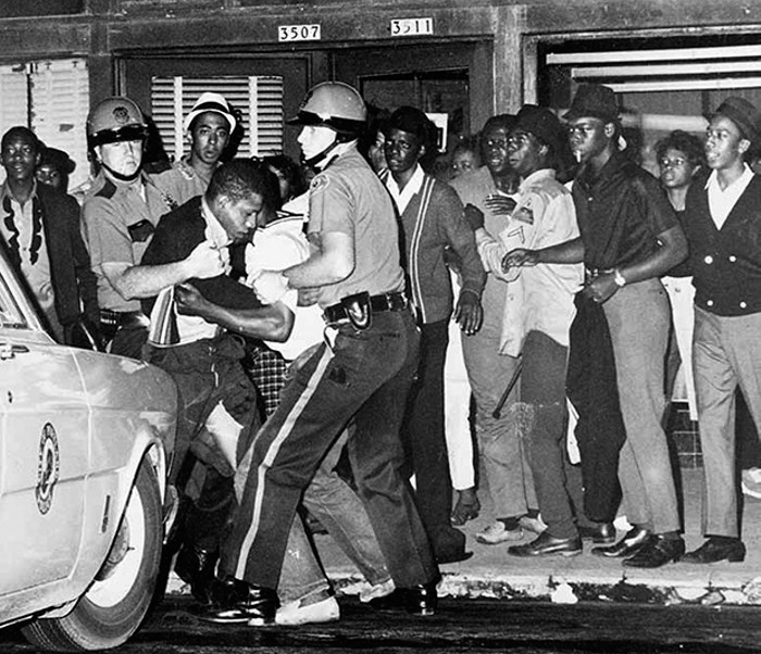 Photo of white policy forcefully grabbing and pulling away black men from a street corner.