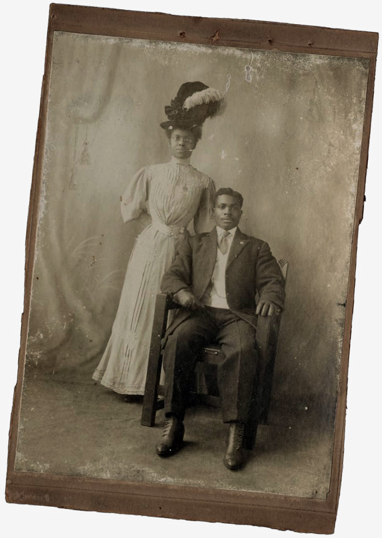 Photo of a black man seated & a black woman standing behind him. They are in formal dress of the late 1800s. Perhaps a wedding.