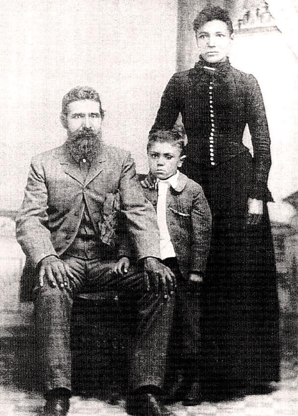 A bearded man sits in a chair with his son and wife standing to his left.