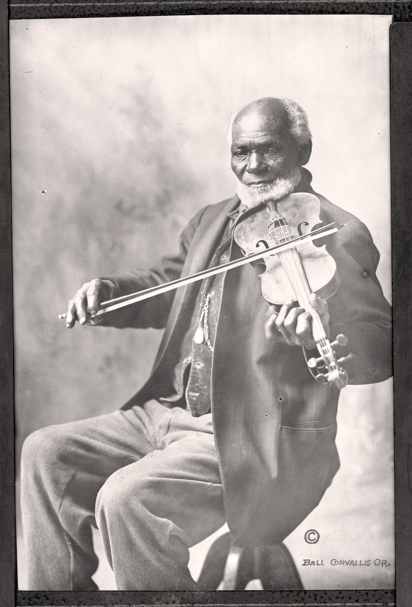 Senior aged black man with white hair, balding on top, plays a fiddle or violin.