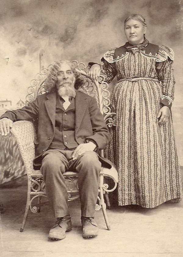 Drury Mathews with long hair and beard and wearing a suit, sits in a wicker chair while Mary stands behind him.