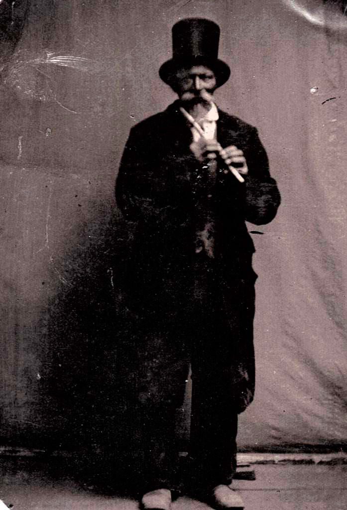 Photo of John Dudley Mathews in a black suit and top hat. He's holding a flute.