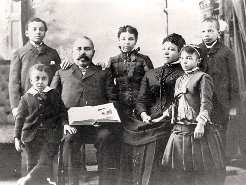 Richard and his wife, America sit in chairs surrounded by their 5 children who are standing.