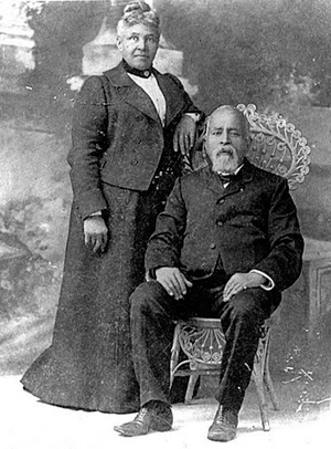 Richard Bogle sits in a wicker chair with his wife, America standing to his right.