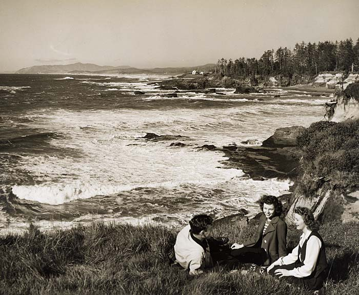 Three people relax on a grassy hillside over looking Boiler Bay.