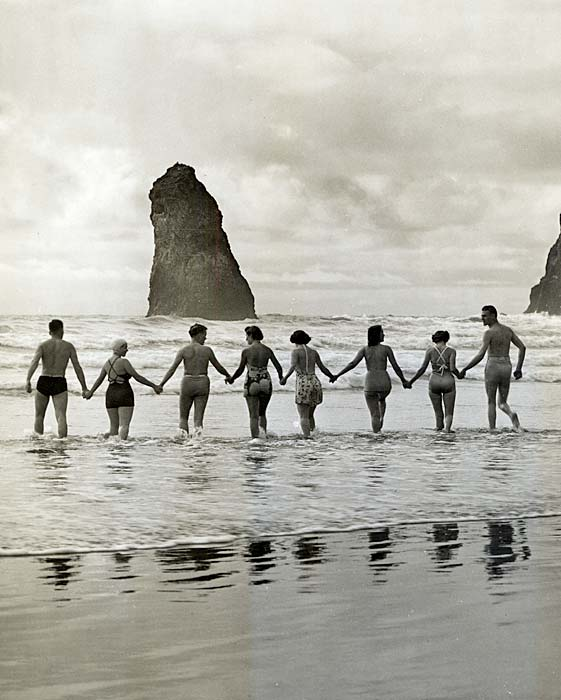 Line of 8 people holding hands walk into the ocean surf in their swim suits in 1940.