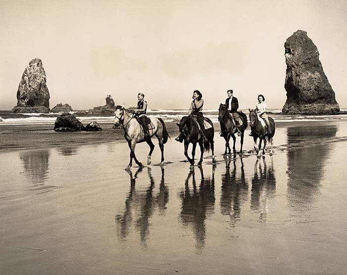 Four people on horseback ride along Cannon beach. Pinnacles of rock stand in the background.
