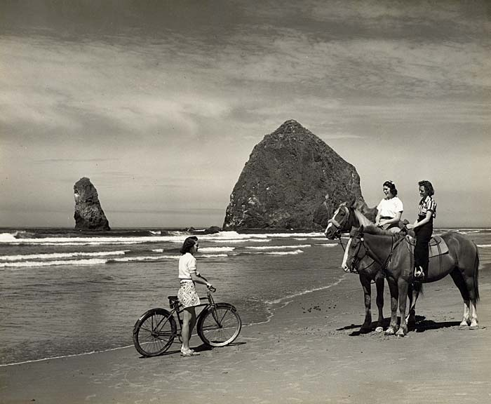 At Cannon Beach with Haystack rock in the back. A woman on bicycle talks with two women on horseback near water on the beach.