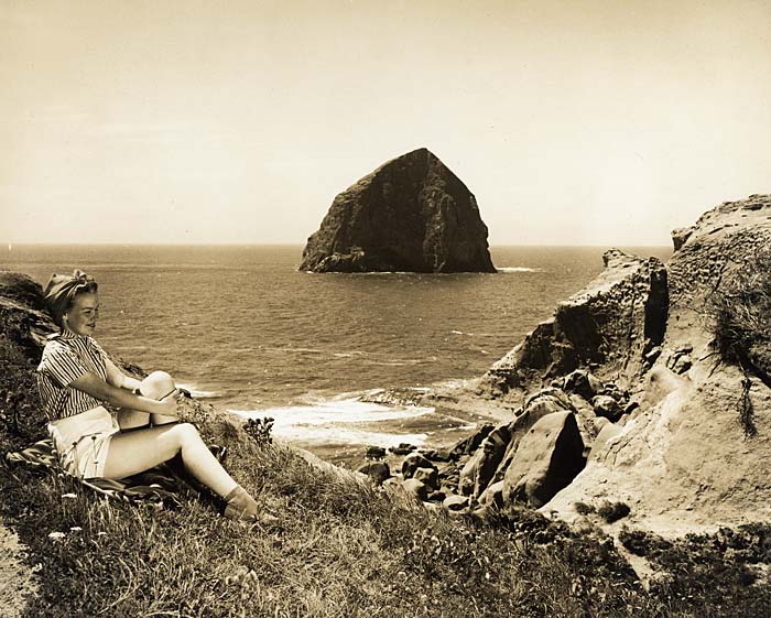 Woman, sitting on a grassy hillside, leans back to admire view of Haystack Rock