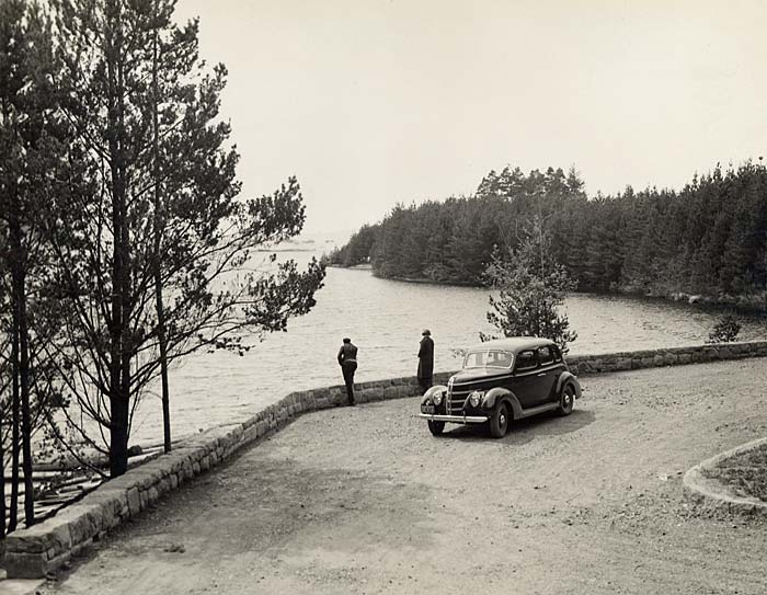 Two people stand outside a car in a turn-around in Honeyman Park overlooking Cleawox Lake.