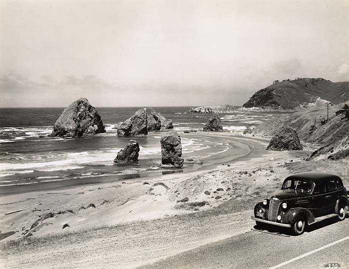 1940 era car drives along highway 101. The ocean is on the left with large rocks jutting out.