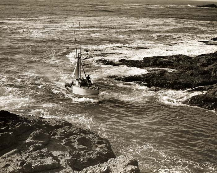 Two men seen on a small boat navigating rough water between a narrow opening in the rocks.