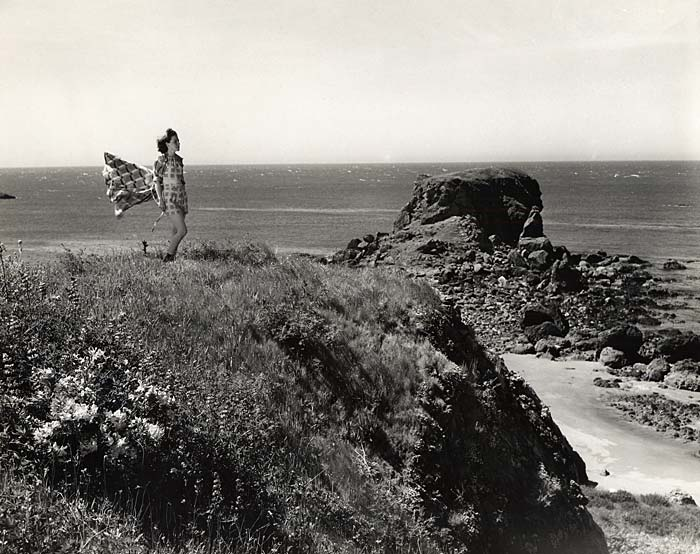 Woman stands on grass covered rock outcrop above the beach. Her wrap flys behind her in the wind.