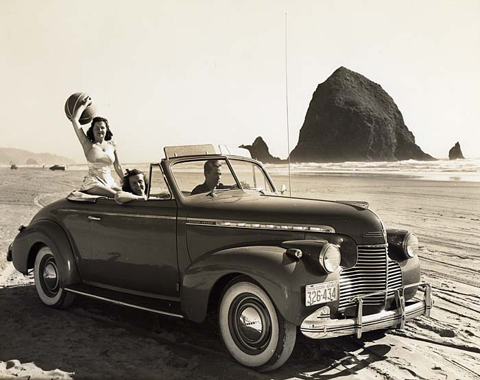 A man drives a Chevrolet along the beach in front of Haystack Rock. Two women ride with him.