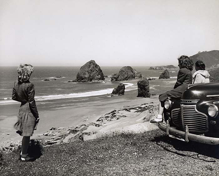 Three women, 1 standing, 2 leaning on a car, look out over the beach.