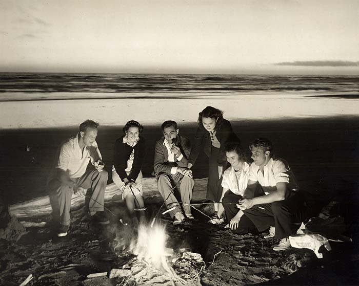 Six people sit beside a fire on the beach. Some sit on a log, some on the sand. They are roasting hotdogs on sticks.