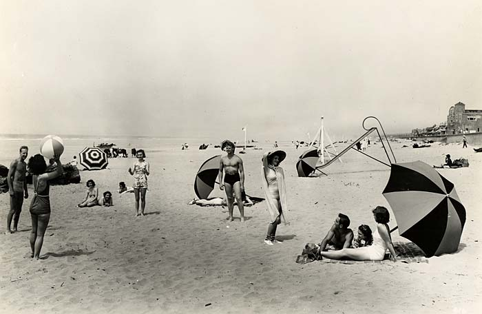 Beach goers play in the sand, toss a beach ball and lounge under umbrellas.