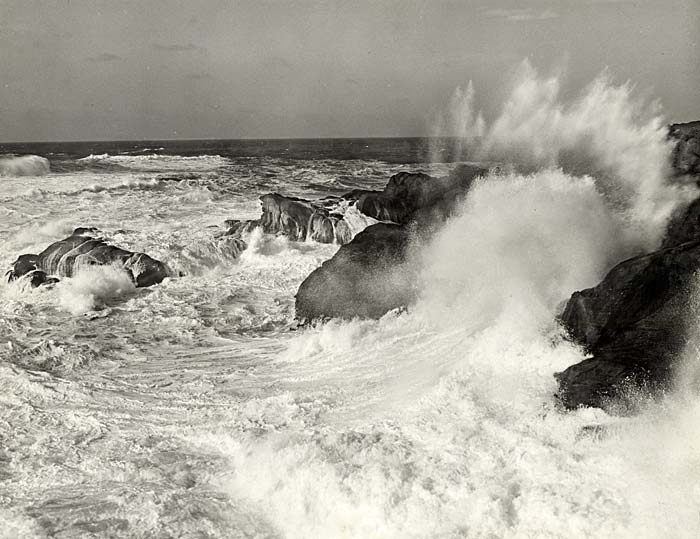 Waves crash against a rocky shore line.