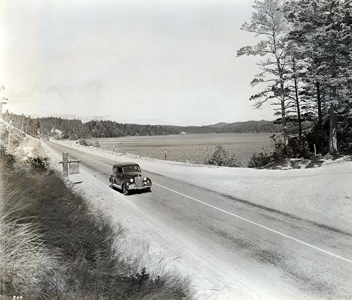 A single car drives along a two lane road with the lake to the right.
