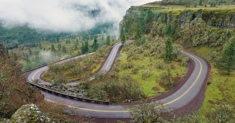 Rowena Loops, a winding road through lush forest land with low level clouds.