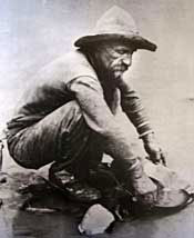 A gold miner squats at a river with a tin plate.