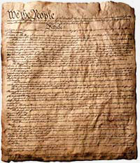 "Worn and wrinkled page from the U.S. Constitution. The only readable words are ""We the People"" and later ""Article 1"""