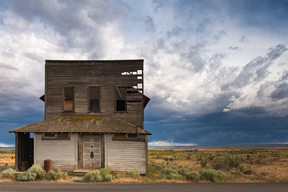 Dilapidated wood plank building on a road side in an open prairie. Storm clouds in the sky.