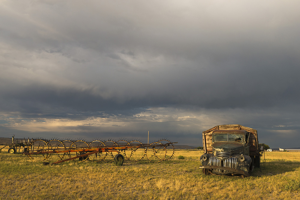 An old truck in a field. An agricultural watering machine rests to the left. Storm clouds in the sky.