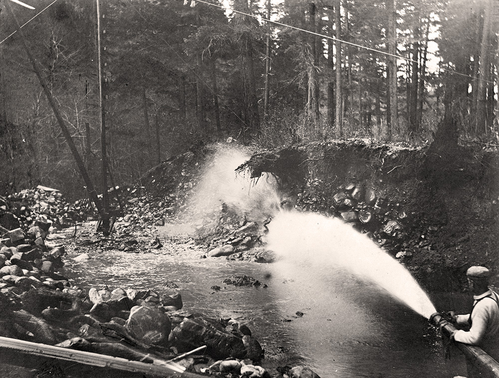 Man stands in a stream aiming a hose of water at a river bank and blasting the rock and dirt away.