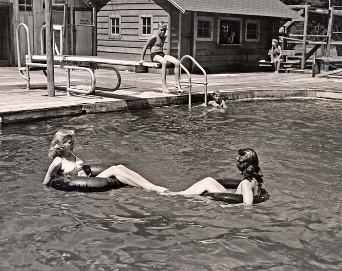 Two women float on rubber tubes in a pool. A boy sits on a diving board with feet hanging over side.