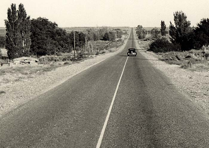 Paved, two lane road stretches to the horizon. One car is seen driving away. Various trees line the side of the road.
