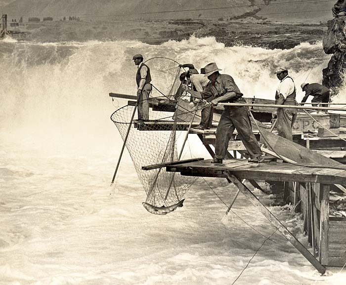 About half a dozen men on wooden shelfs stand with nets out over the falls.