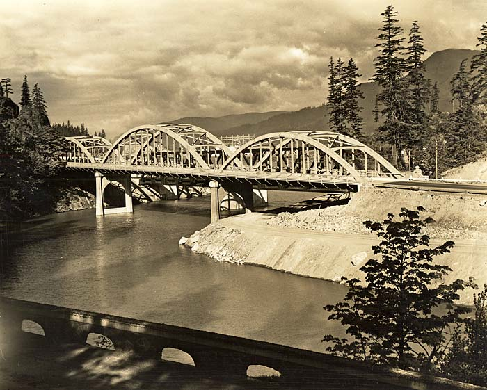 Eagle Creek Bridge spans a river with tall fir trees on each side and tall mountains in the background.