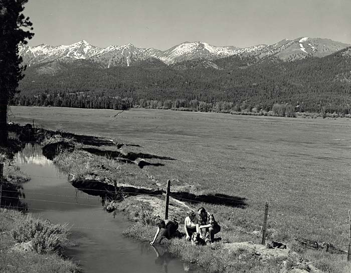 Three people squat near an irrigation ditch. The Elkhorn Mountains are in the background.