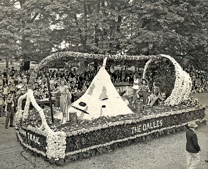 A float in the rose festival parade from The Dalles features women partaking in recreational activities such as skiing, fishing.