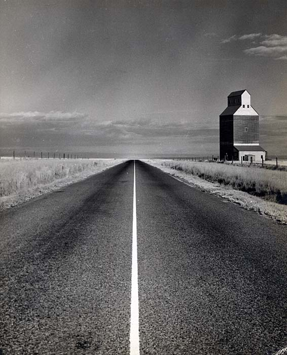 A 2 lane paved road extends to the horizon. A grain elevator is seen to the right in a field.