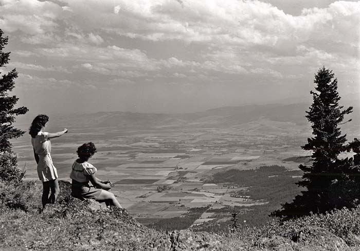 Two women sit on a hillside of Mt. Emily and look out over the Grande Ronde Valley.