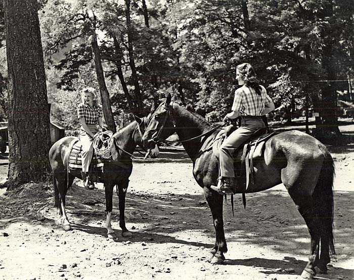 Two women sit on horseback in a forested area.