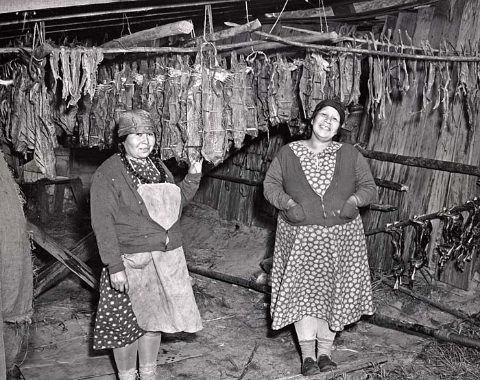 Two Native American women in dresses stand in a fish drying room and smile for camera.