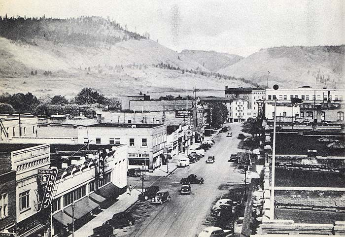 View from above of the main road in La Grande in 1940. Old cars drive on a road lined with businesses. Rolling hills in the back
