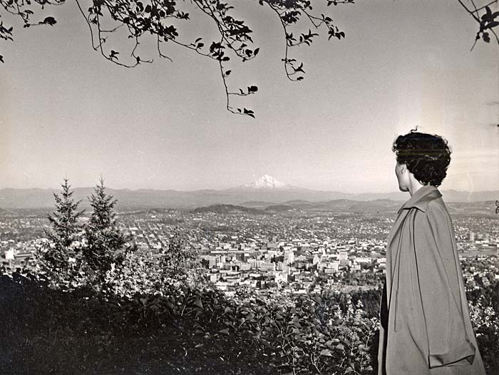 Woman stands to the right looking over Portland from above. Mt. Hood's snowy peek shows in the distance.