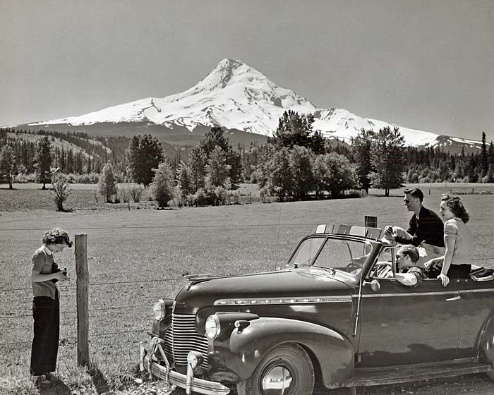 Three young adutls pose for a photo in a 1940s car while another young adult takes a photo. Mt. Hood's snowy top shows in back.