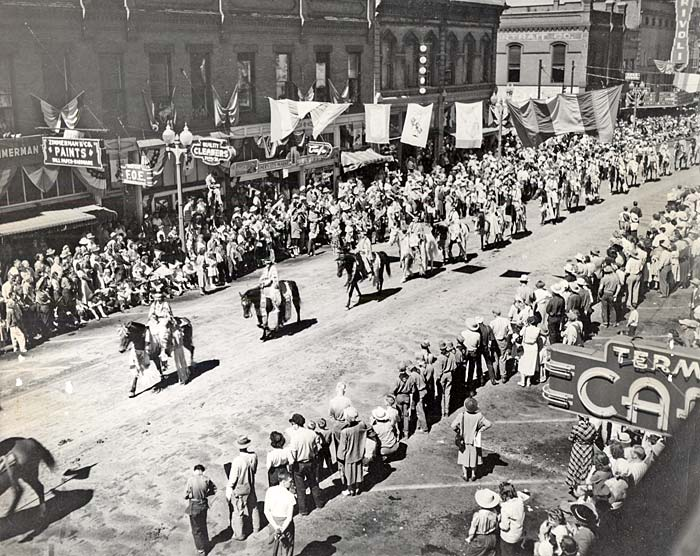 A single file line of a dozen or more horses with riders streams down the middle of a street lined with spectators.